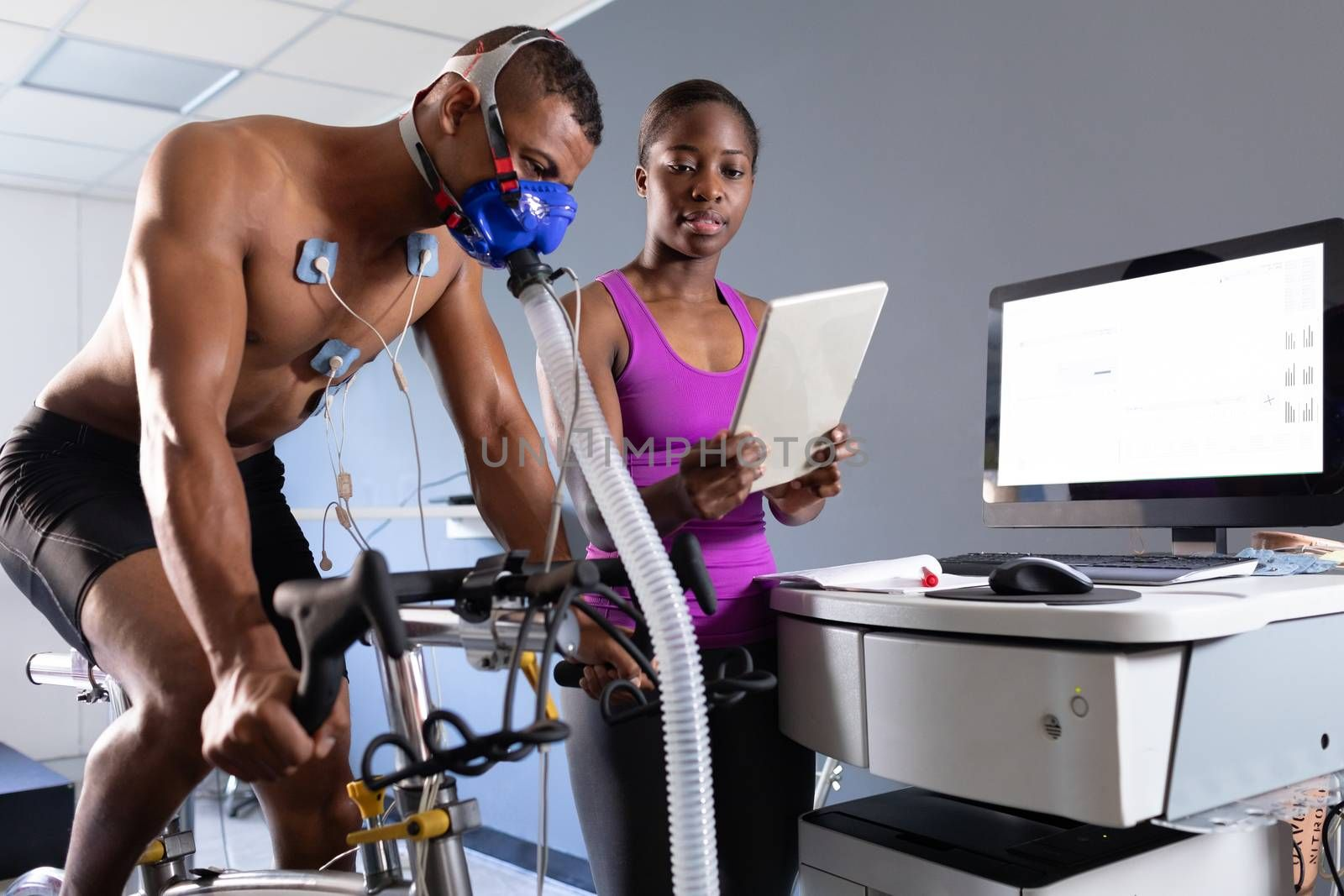 Side view of a naked African-American athletic man doing a fitness test using a mask connected to a monitor while riding an exercise bike and an African-American woman showing him the results inside a room at a sports centre. Bright modern gym with fit healthy people working out and training. Athlete testing themselves with cardiovascular fitness test on exercise bike