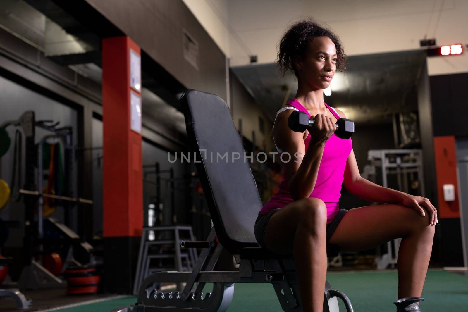 Side view of an African-American woman holding a dumbbell while sitting inside a room at a sports centre. Bright modern gym with fit healthy people working out and training. Bright modern gym with fit healthy people working out and training