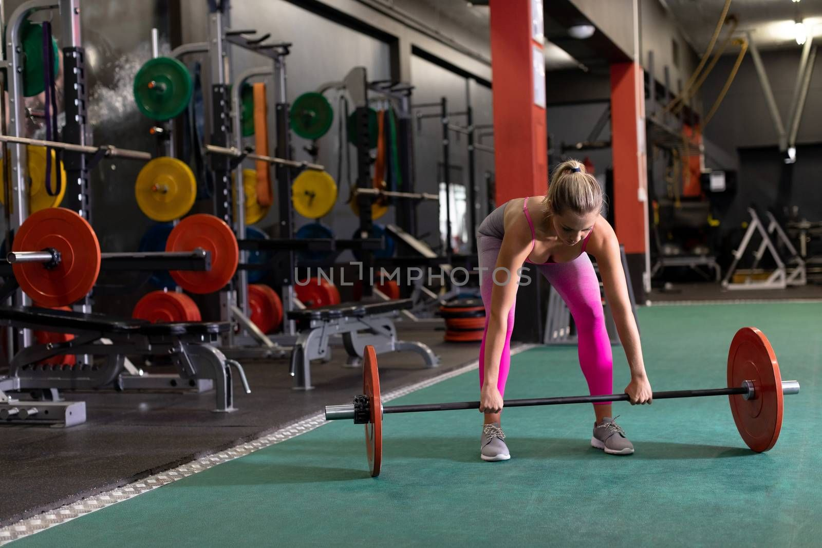 Front view of a Caucasian woman lifting weights inside a room at a sports centre. Bright modern gym with fit healthy people working out and training. Bright modern gym with fit healthy people working out and training