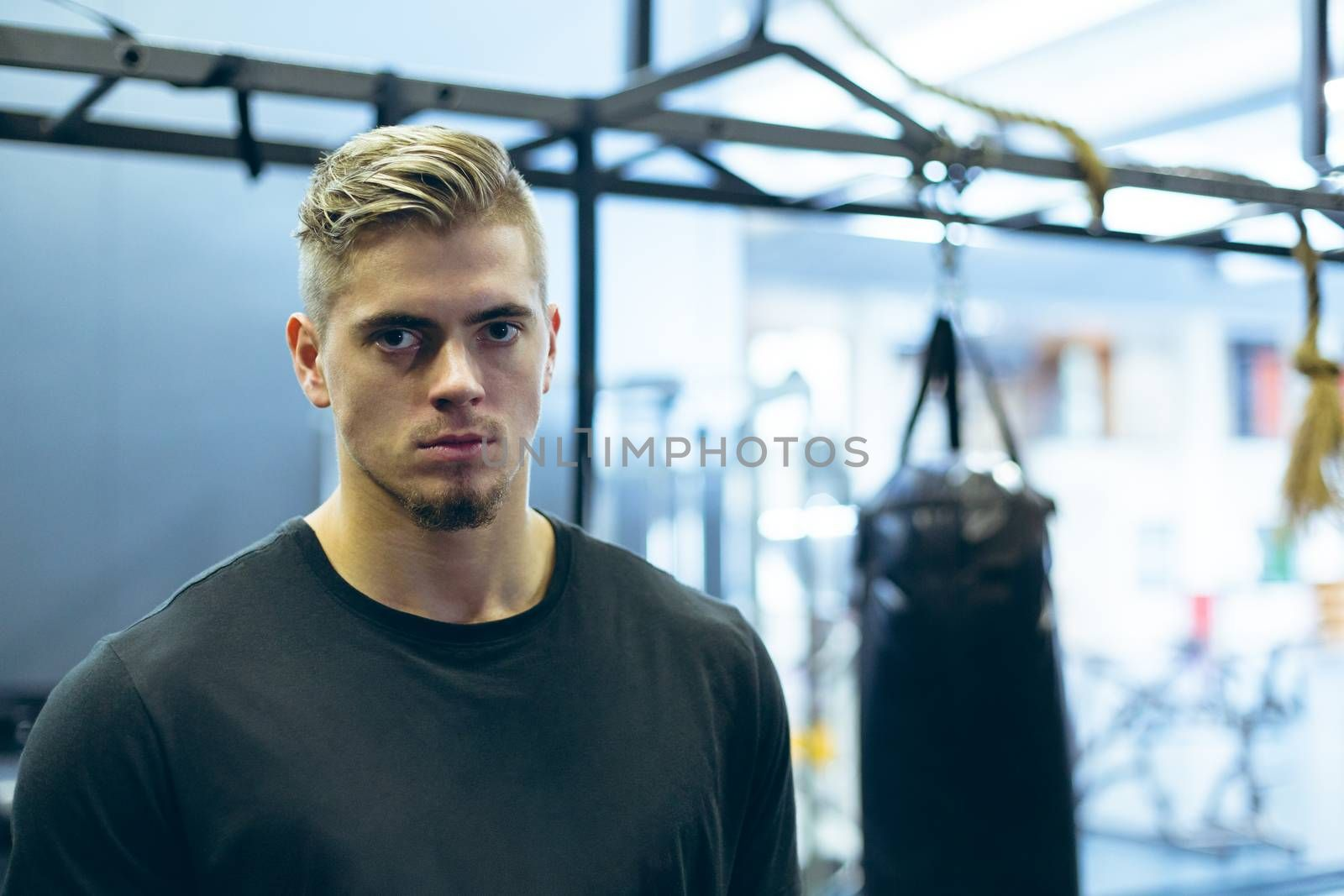 Portrait of handsome young Caucasian male athletic looking at camera in fitness center. Bright modern gym with fit healthy people working out and training