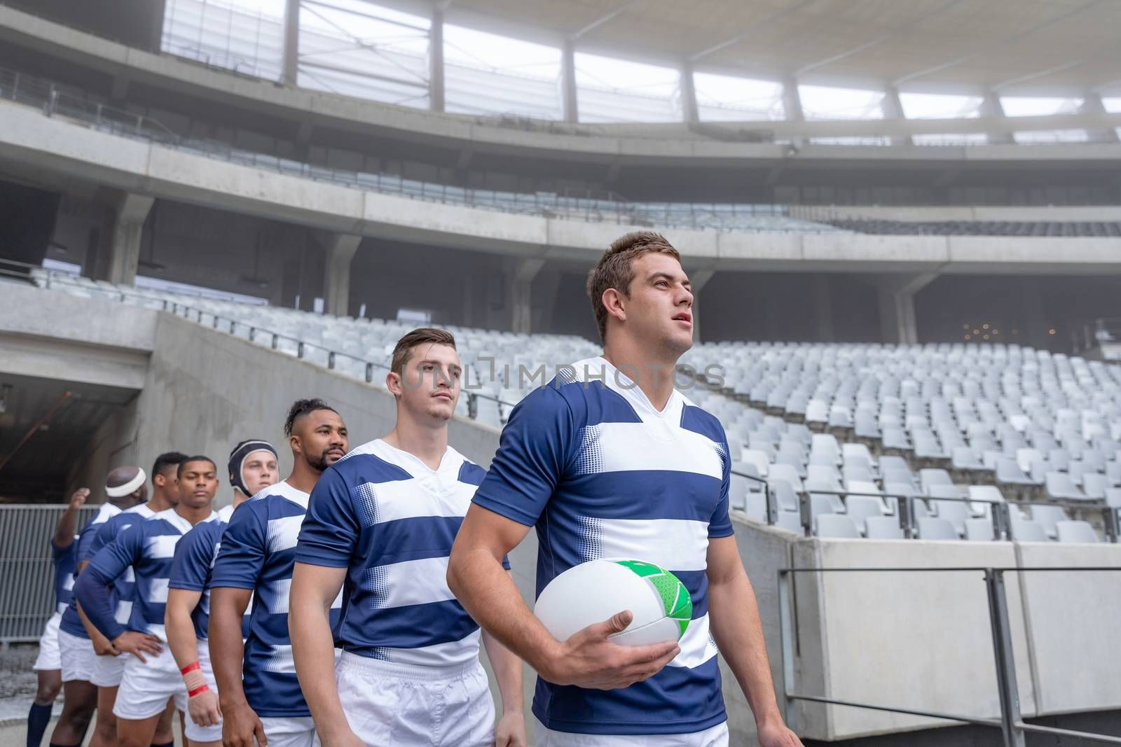 Side View of group of diverse rugby players entering stadium in a row for match
