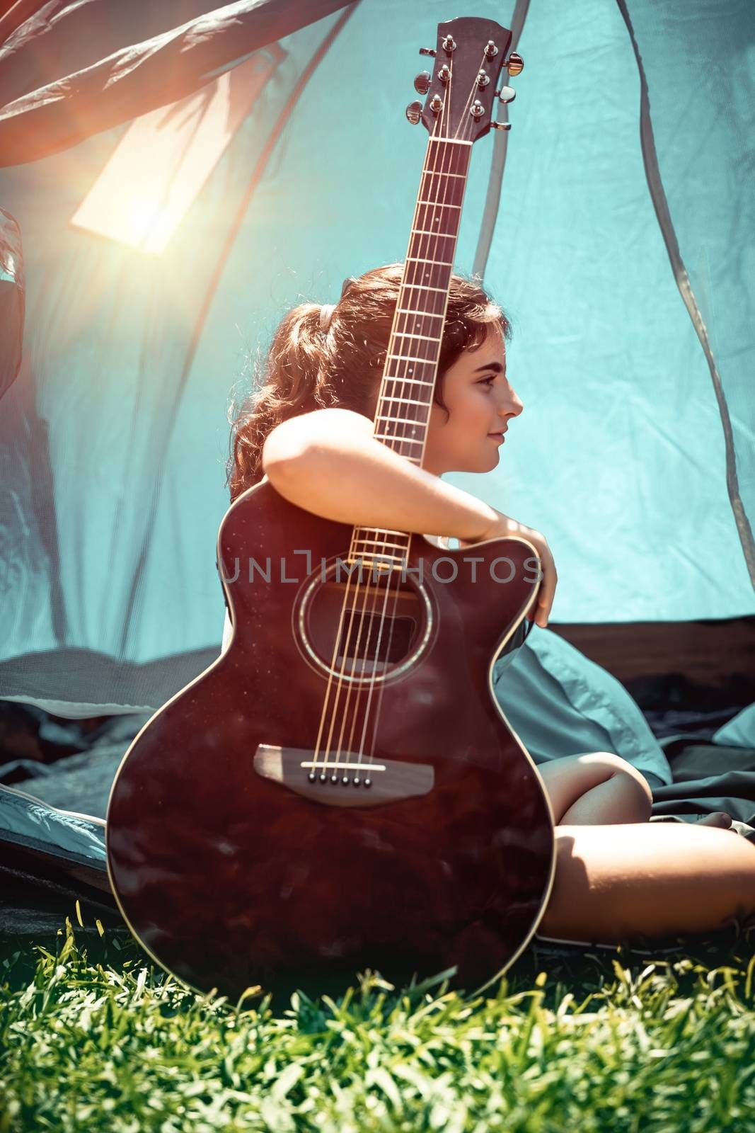 Teen girl with pleasure spending holidays in summer camp, pretty child sitting with a guitar near the tent, singing song and having fun in sunny summertime day