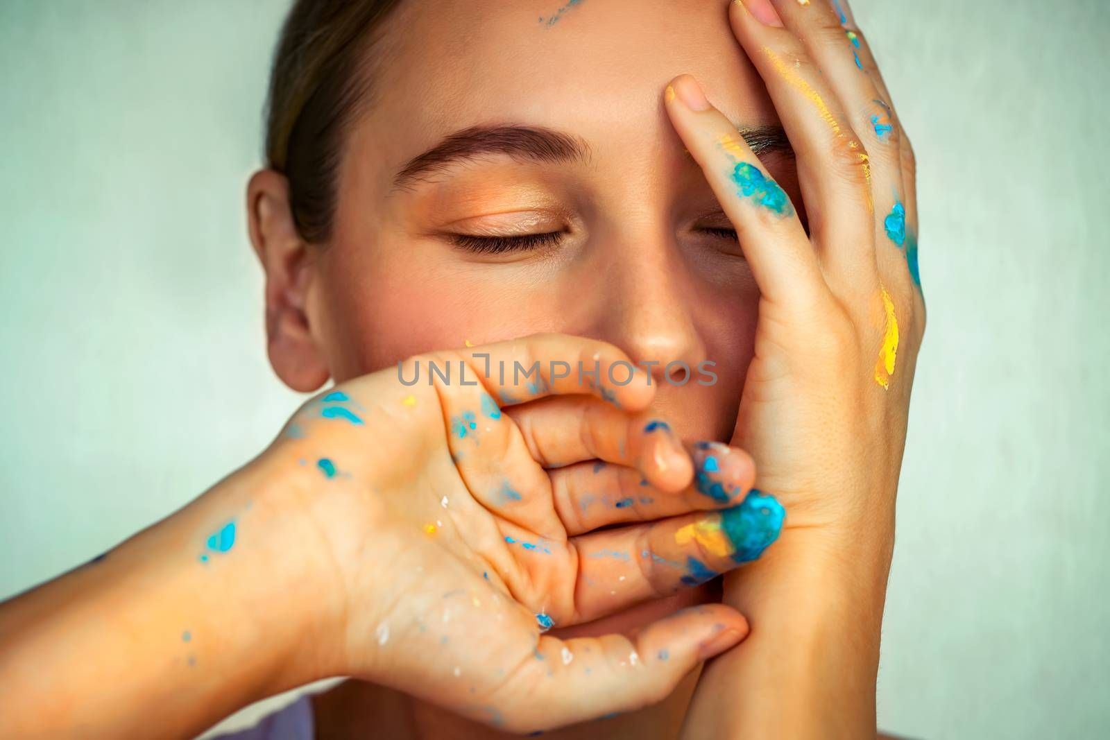Conceptual photo of creativity and art, beautiful woman with a dreamy face and paint-stained fingers, mindfulness, and visualization on a new idea