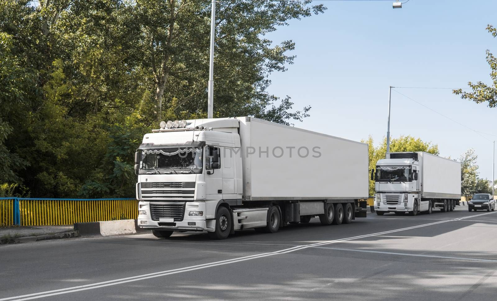 Two trucks on a road against blue sky and trees, cargo transportation concept