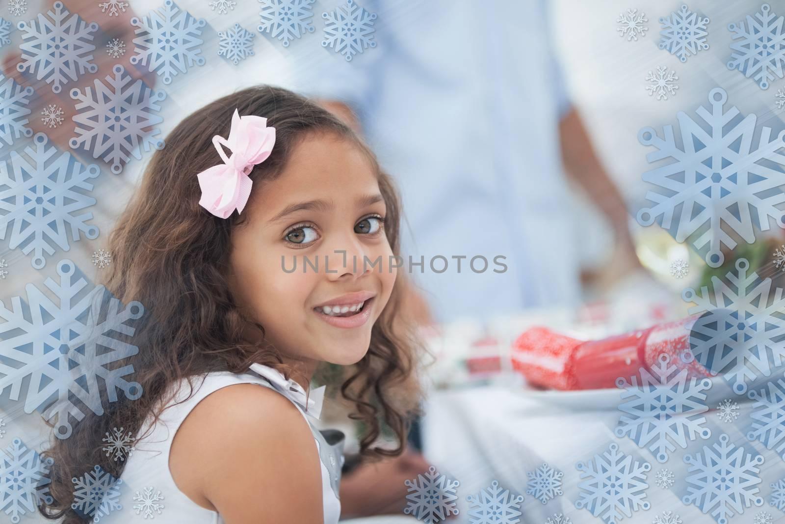 Little girl sitting at table for christmas dinner against snowflake frame