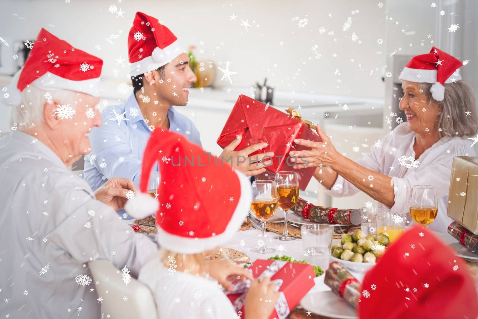 Composite image of Happy family exchanging christmas gifts against snow falling