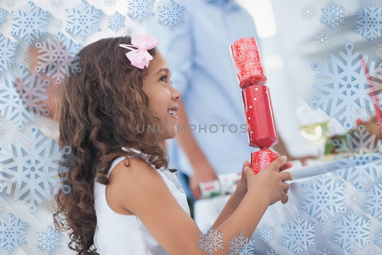 Cute little girl holding crackers against snowflake frame