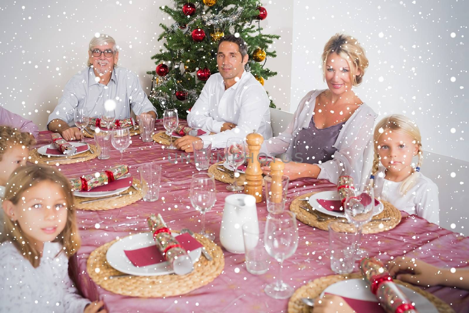 Composite image of Smiling family at the dinner table against snow falling