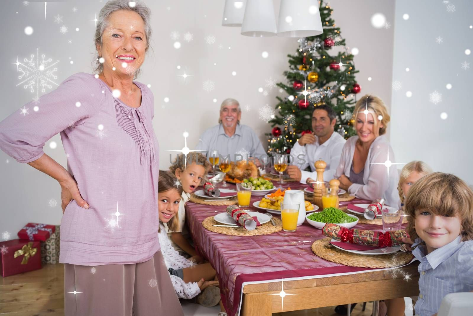 Composite image of Grandmother standing beside dinner table against snow falling