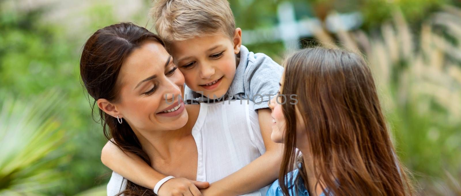 Portrait of a beautiful young mother with her two cute kids having fun outdoors, happy family with pleasure spending time together, enjoying summer holidays