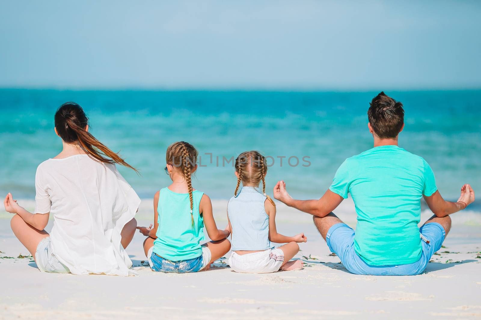 Family in yoga on the beach