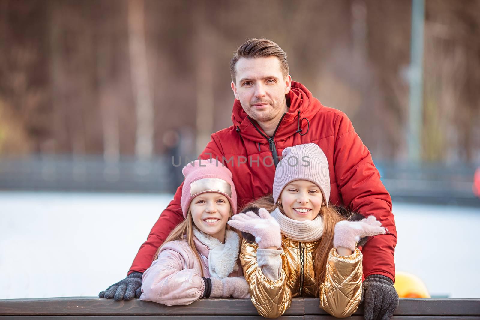 Family winter sport. Family skate on the ice-rink
