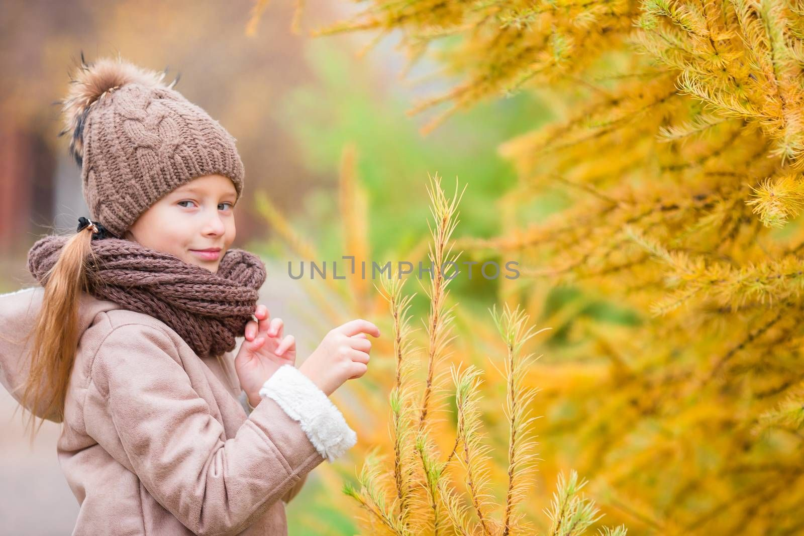 Adorable little girl at beautiful autumn day outdoors