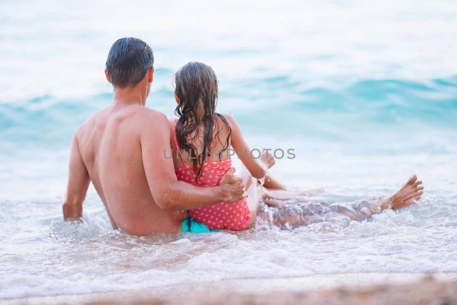 Family swim in waves. Summer family vacation