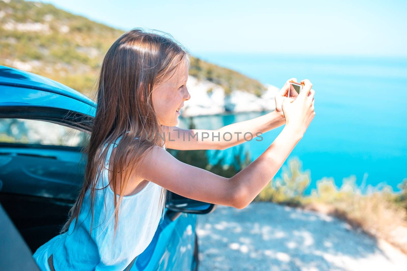 Little girl traveling by car and making photo of beautiful nature. Summer holiday and car travel concept