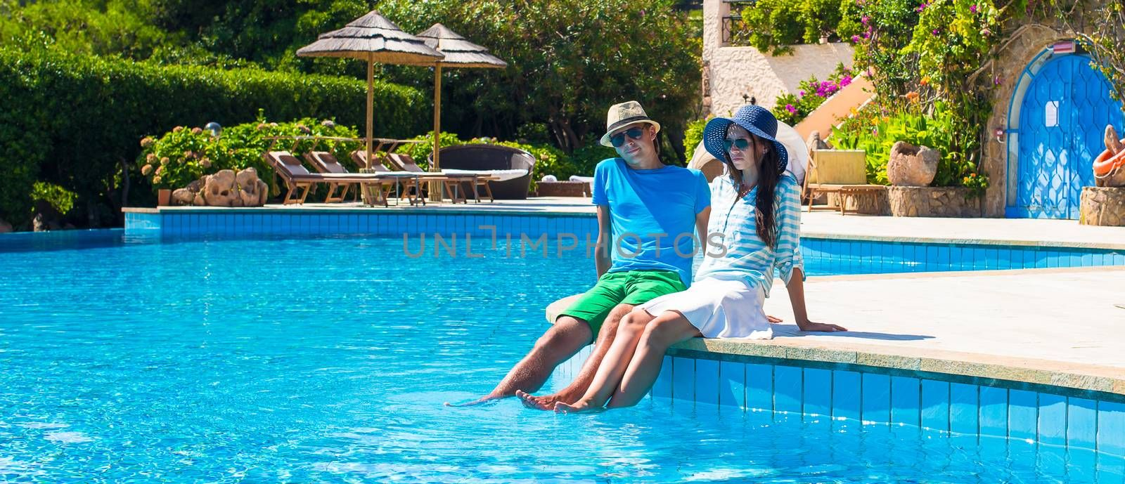 Lovely young romantic couple relaxing by the pool