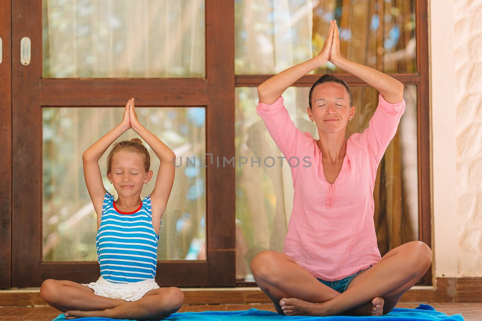 Family meditation in yoga club. Mother and daughter doing yoga exercise outdoors