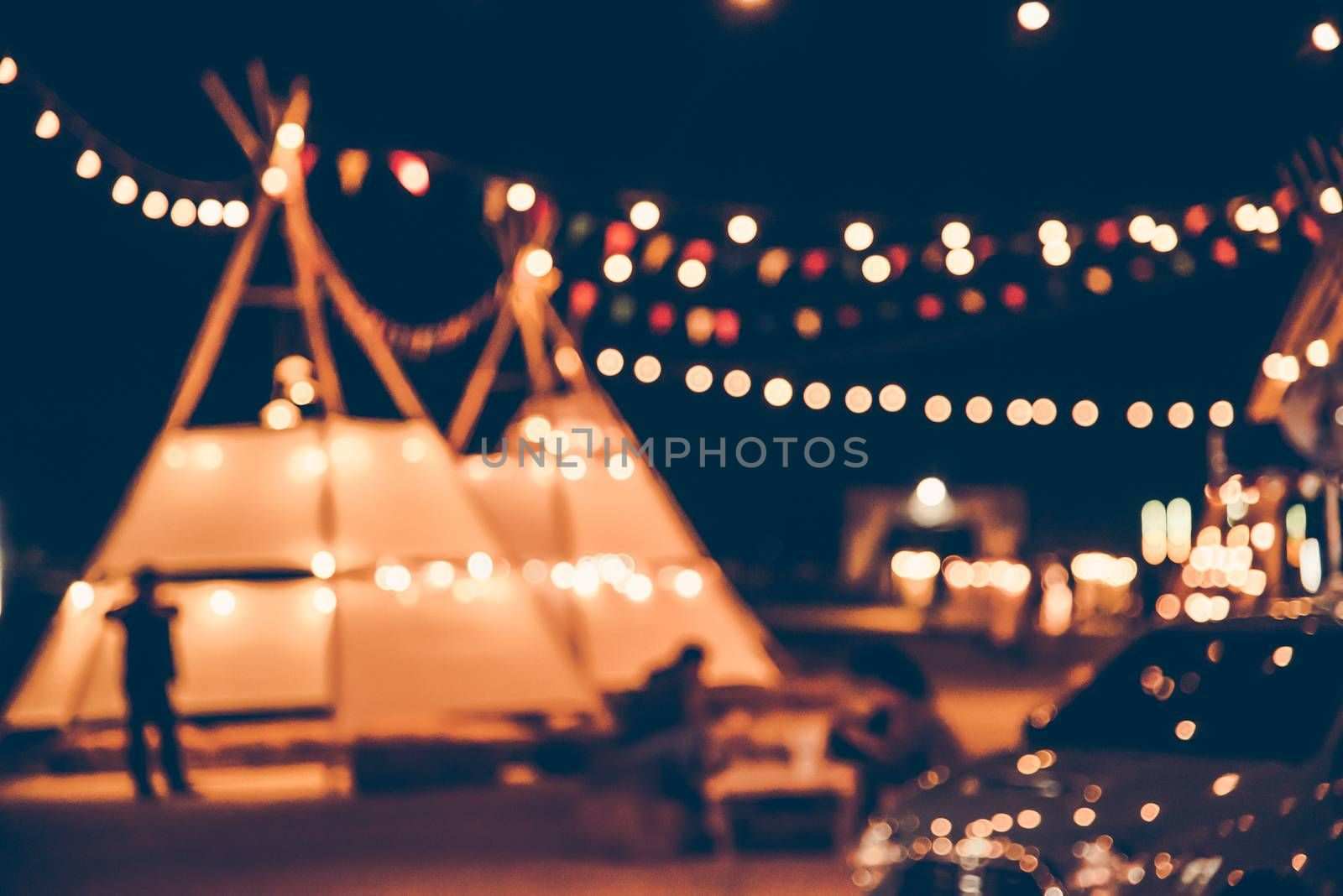 Blurred images of the background party in the festive festivities during the night, consisting of people and glittering bokeh.