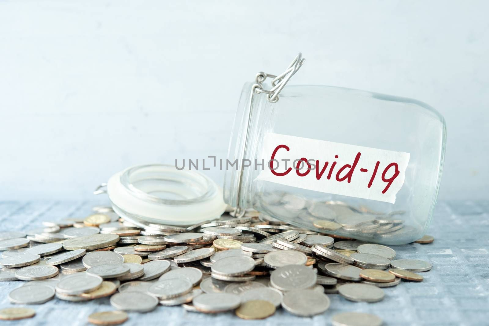 Coins in glass money jar with covid19 label, financial concept.