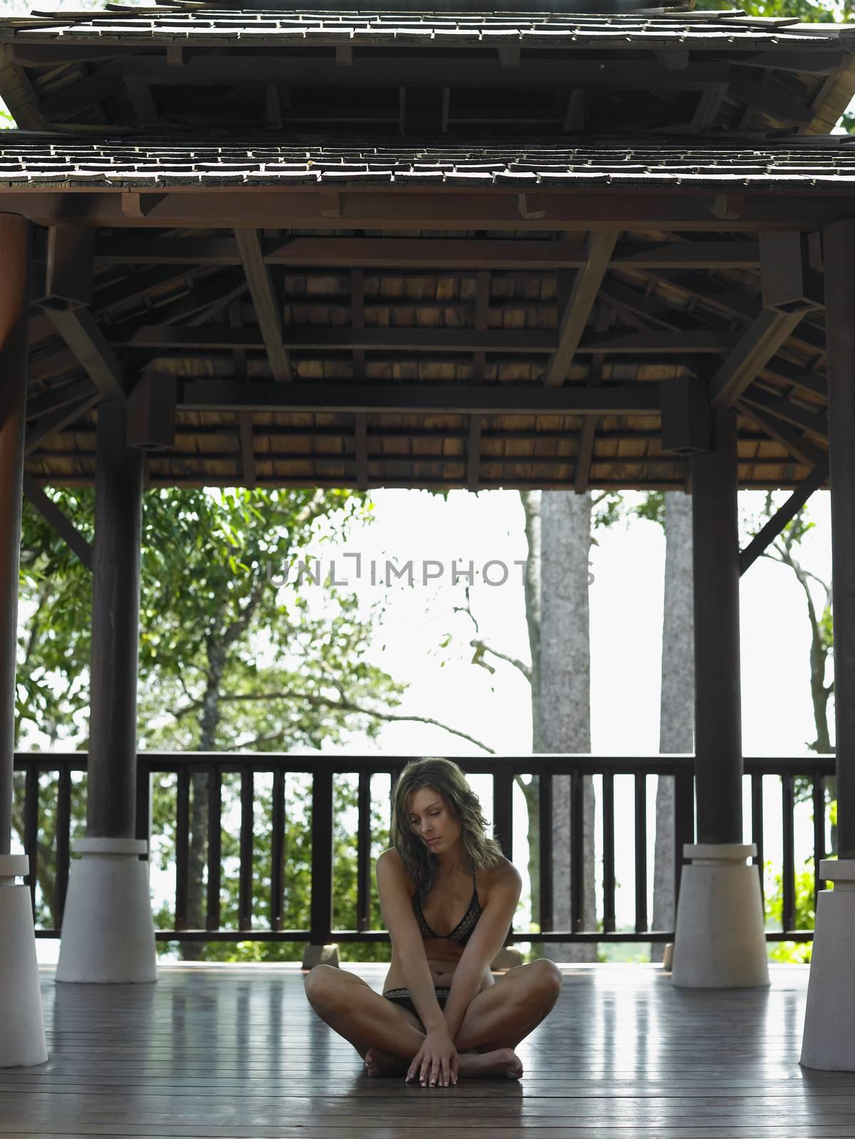Thailand young woman in bikini sitting on floor