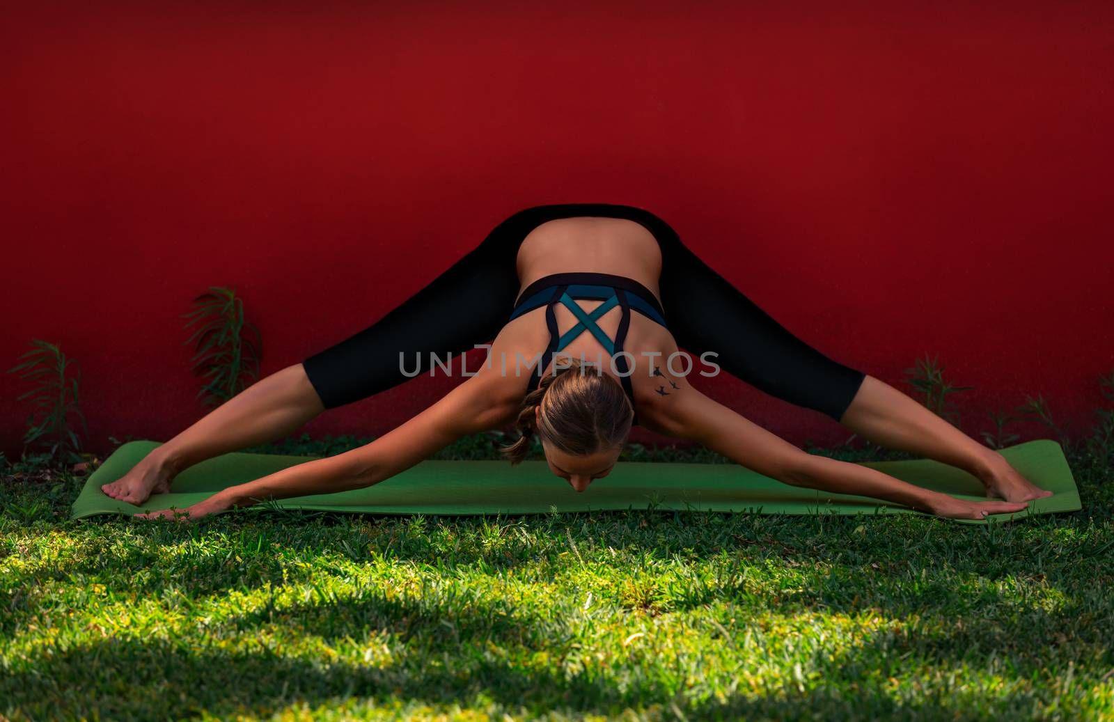 Sportive Young Woman Doing Yoga Exercises Outdoors Over Red Background. Prasarita Padottanasana. Wide-legged Forward Fold. Healthy Lifestyle Concept.