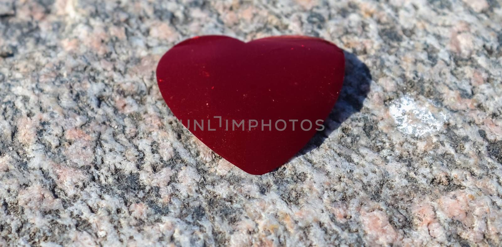 Romantic red love heart lying on a granite background
