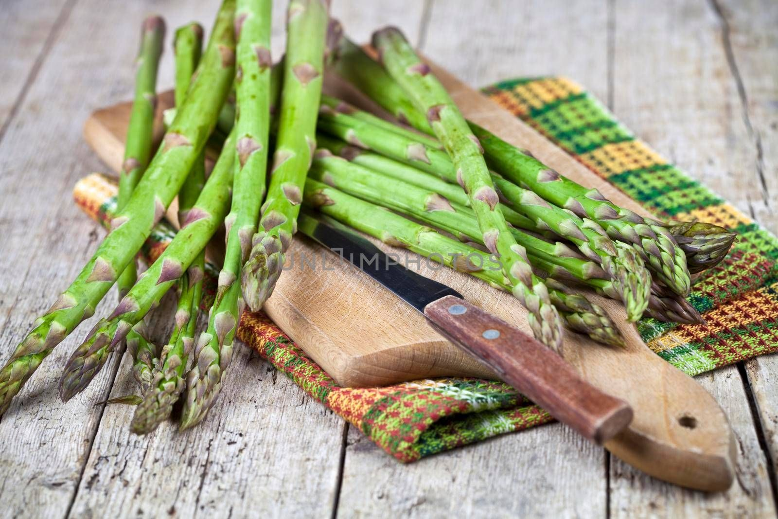 Fresh raw garden asparagus and knife closeup on cutting board on rustic wooden table background. Green spring vegetables and cotton napkin. Edible sprouts of asparagus.