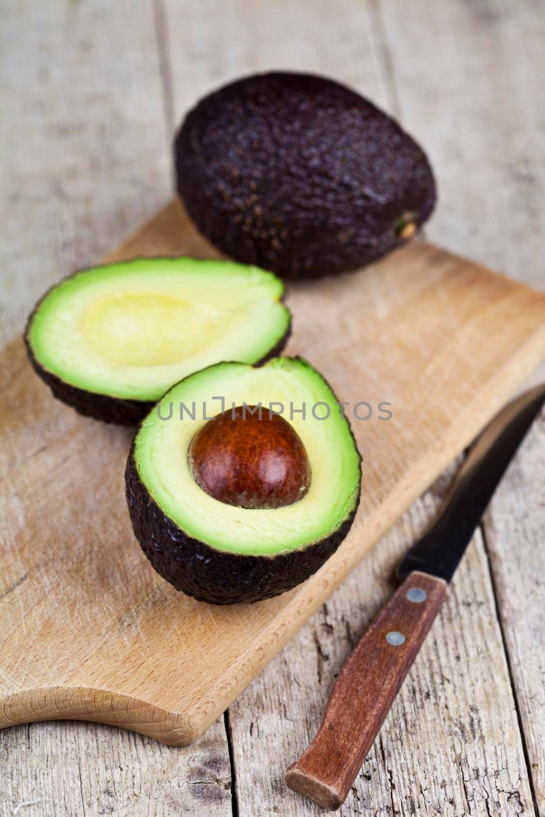 Avocado and knife on cutting board on old wooden table background. Fresh avocado halves on rustic wooden backround with copy space. Healthy food concept.