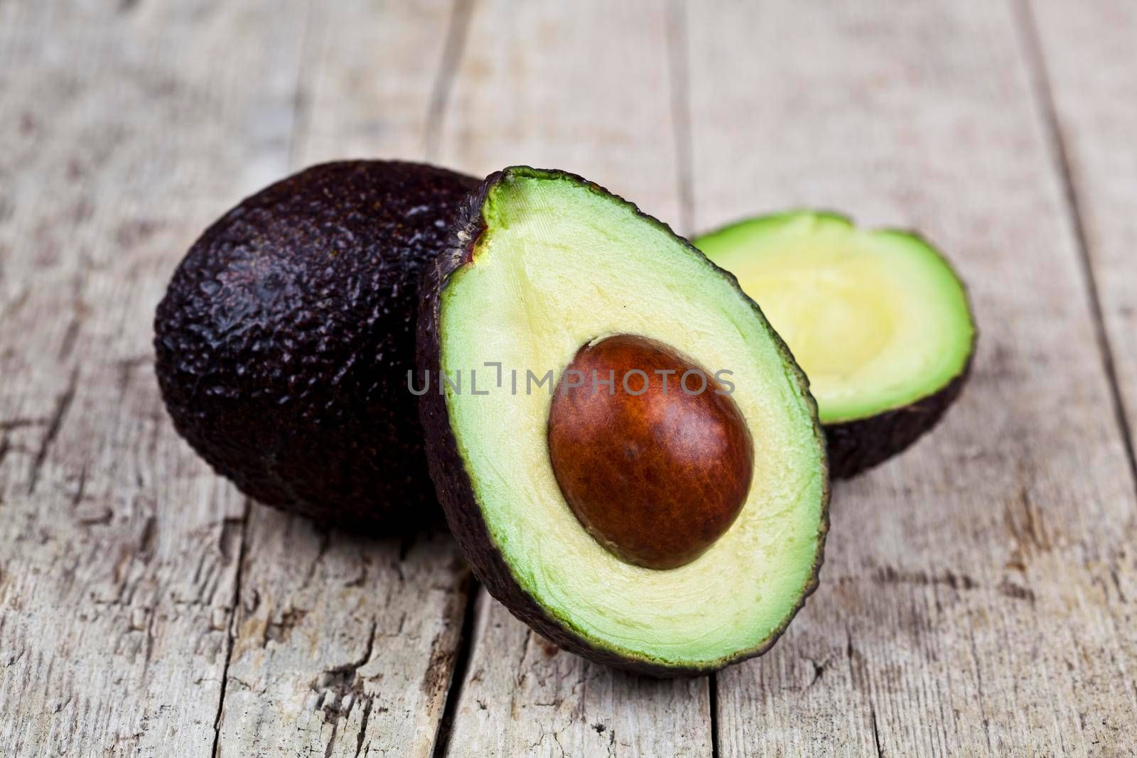 Fresh organic avocado on old wooden table background. Fresh avocado halves on rustic wooden backround. Healthy food concept.