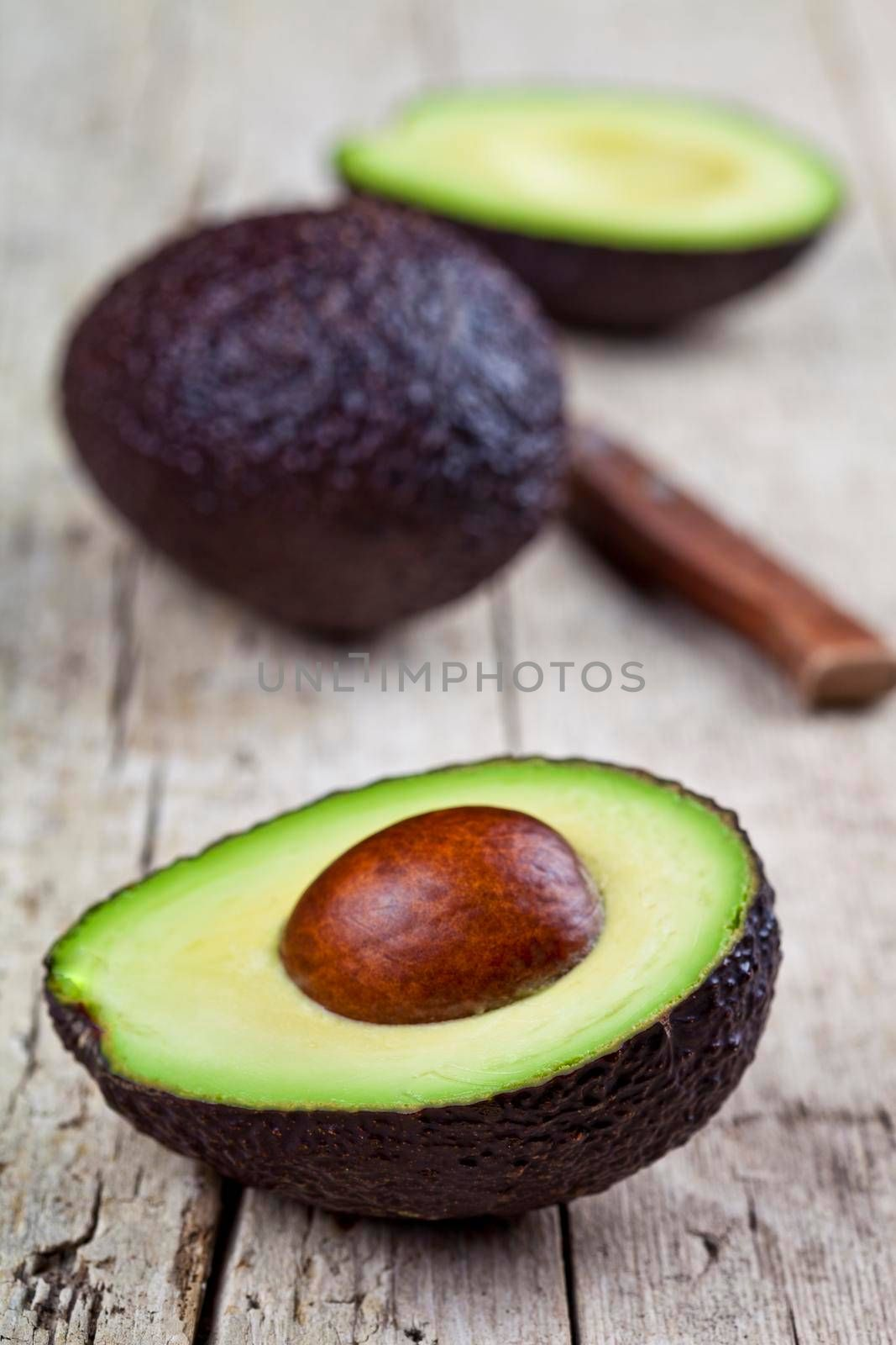 Fresh avocado and knife on old wooden table background. Fresh avocado halves on rustic wooden backround. Healthy food concept.