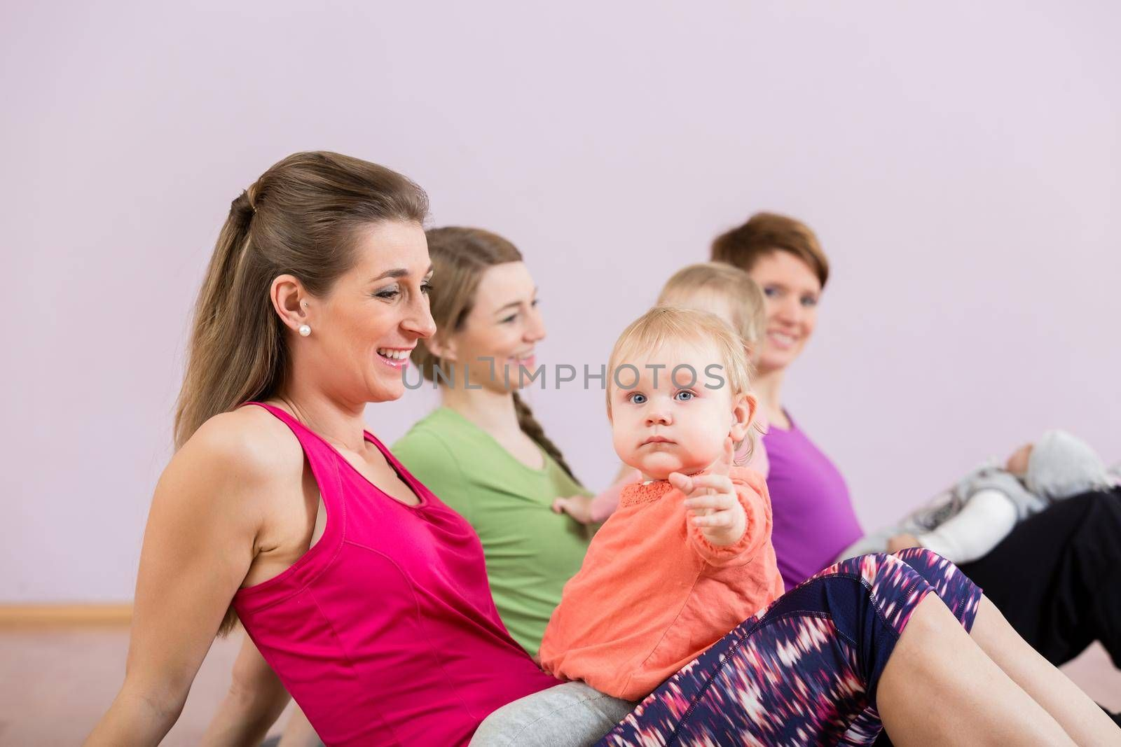 Mothers exercising with their babies at postnatal exercise course