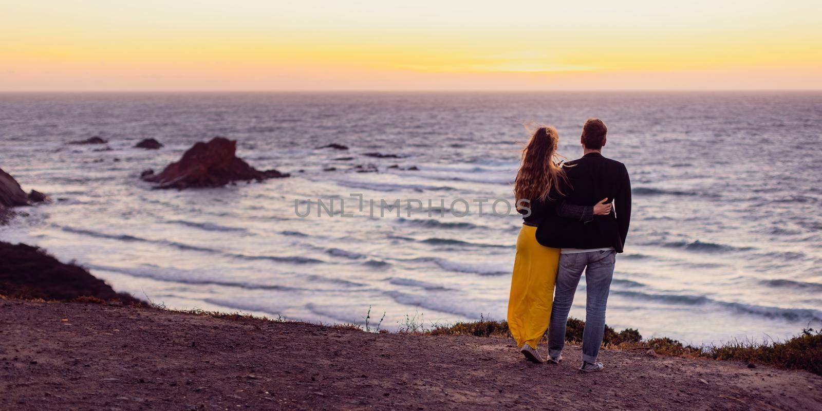 Romantic couple in love embracing each other during sunset at beach