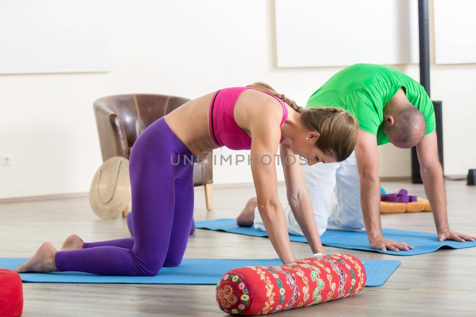 Young couple performing yoga pose on exercise mat in yoga class