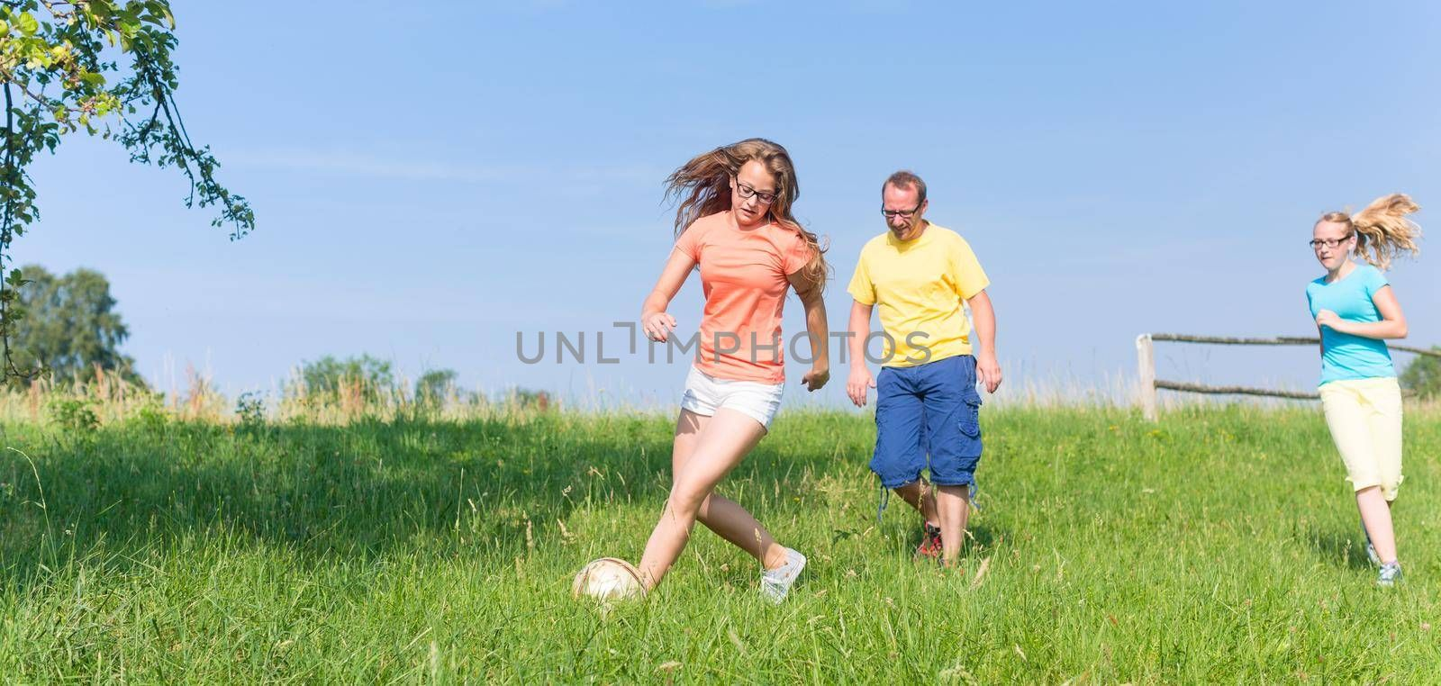 Family playing soccer on meadow in summer