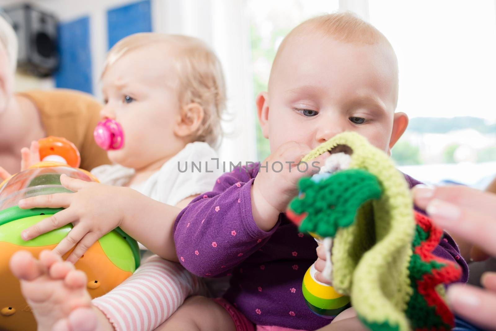 Babies with pacifier in toddler group playing with toys