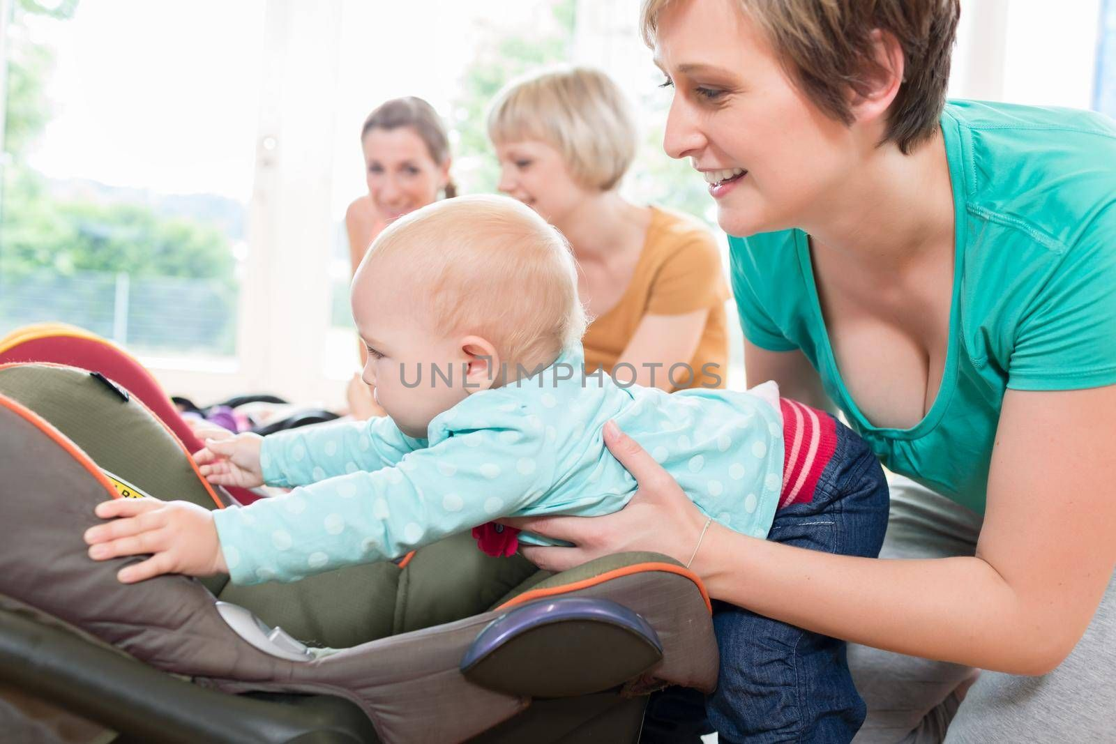 Moms and babies in mother and child course practicing with baby seats
