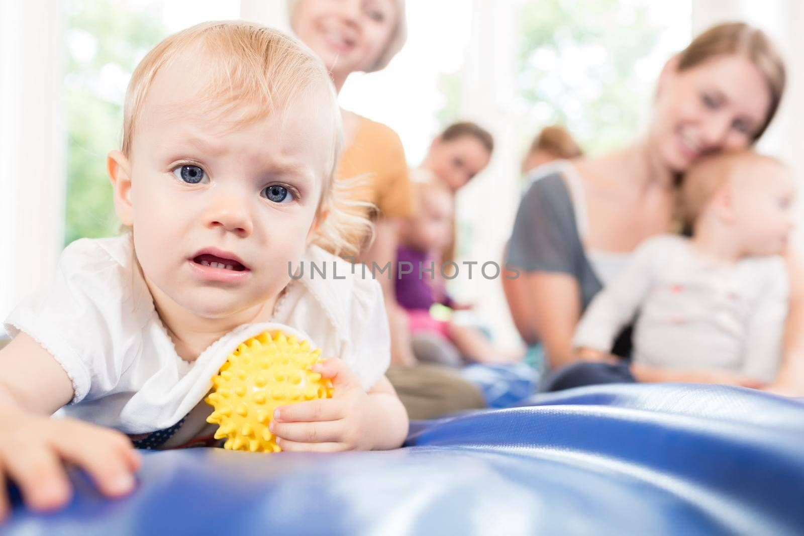 Babies and moms in postnatal mother and child course playing