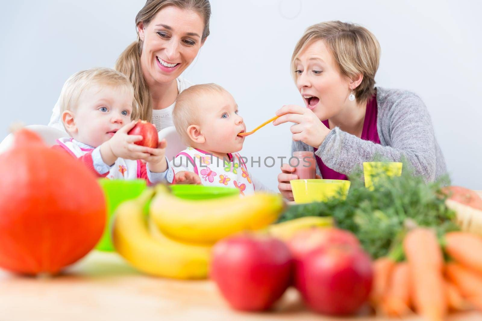 Two happy mothers and best friends smiling while feeding together their healthy baby girls at table with natural and nutritive food indoors at home