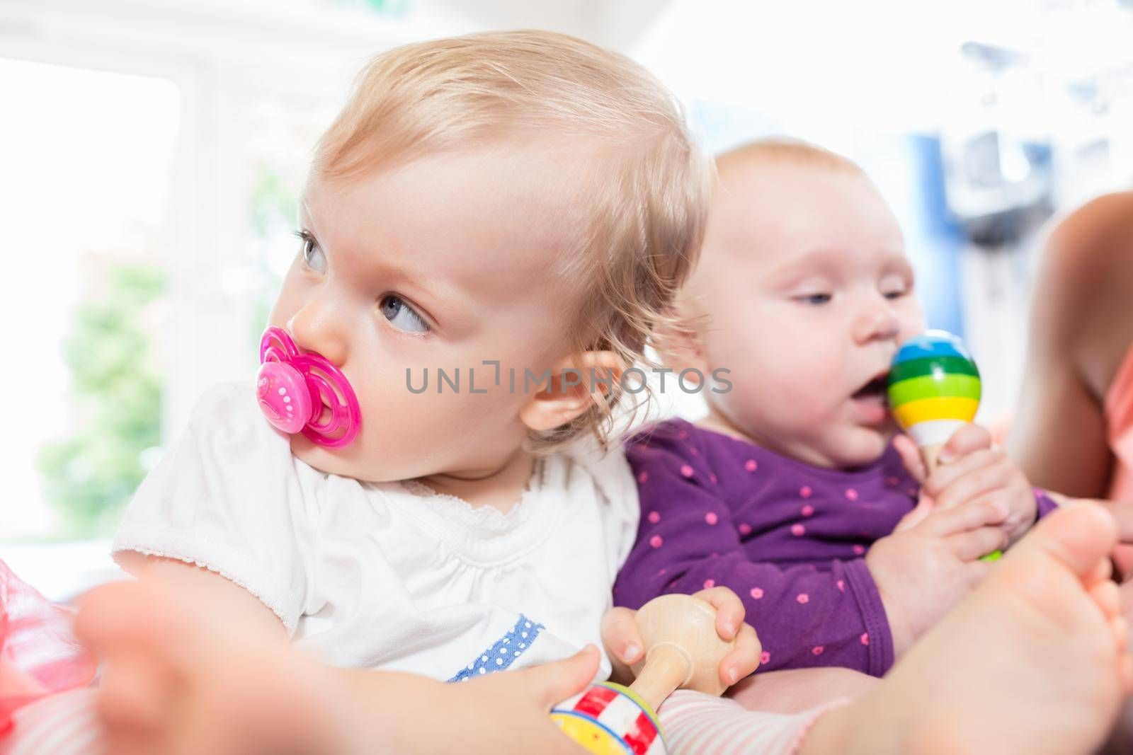 Babies with pacifier in toddler group playing together with toys
