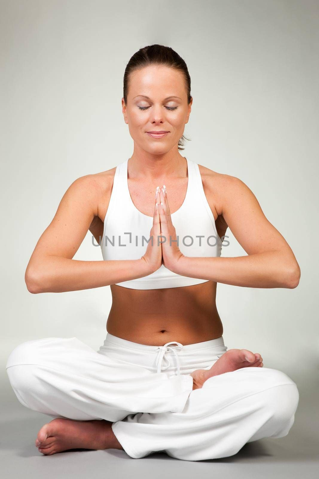 Young woman in a yoga position (Lotus seat)