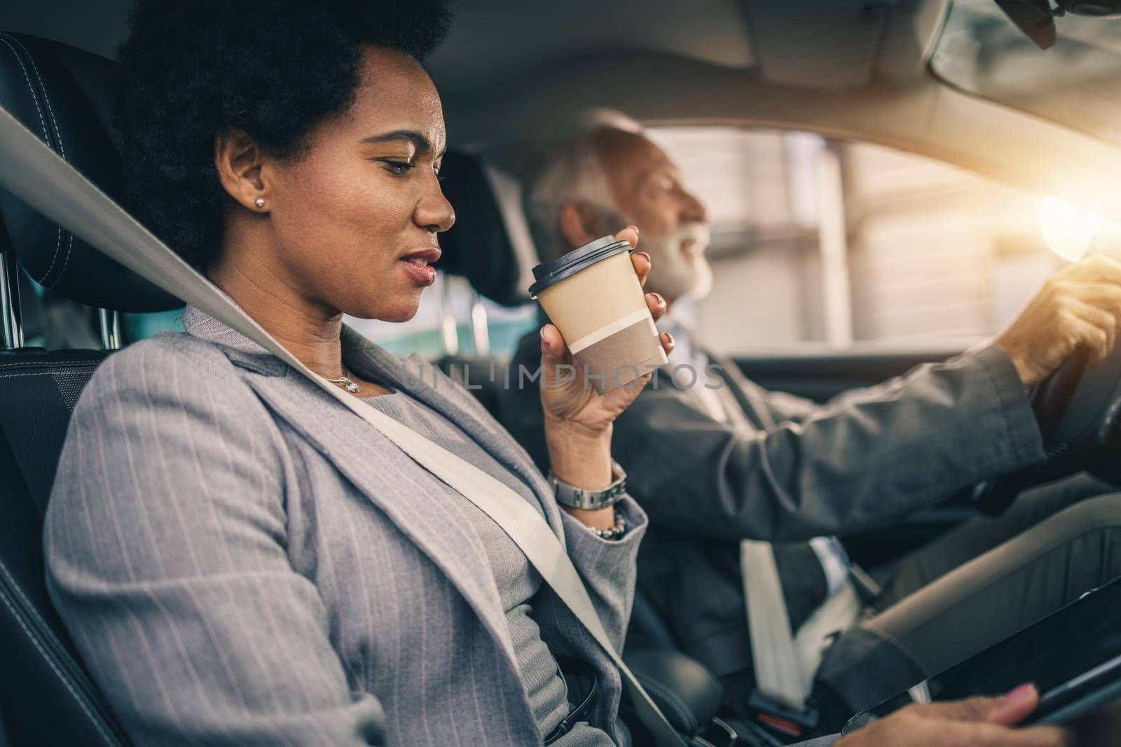 Shot of a successful black business woman drinking coffee to go and using digital tablet during her morning commute.