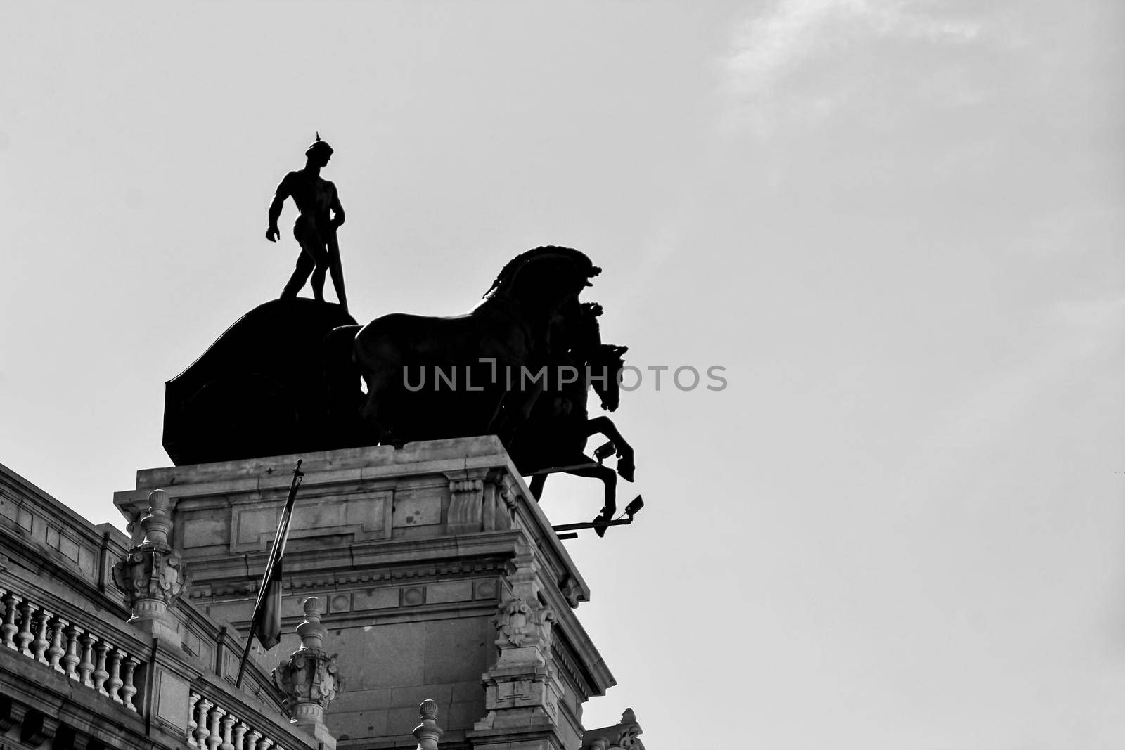 Beautiful quadriga statue on the roof of a building in Madrid