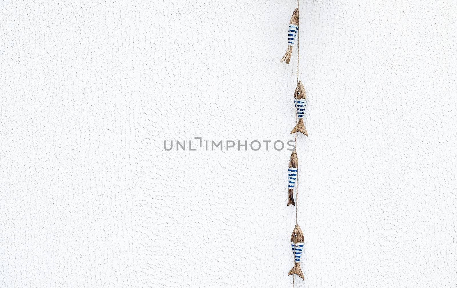 Beautiful Clean White Background with Cute Little Wooden Fishes Decoration on the Side. Stylish Beach House Decor. Summertime Wallpaper.