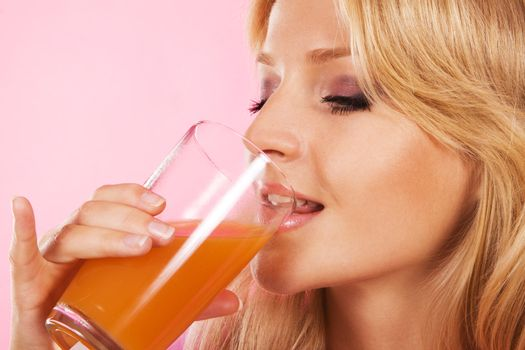 Closeup portrait of a lovely blonde drinking fresh juice