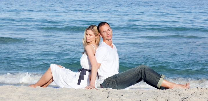 Romantic couple sitting on the sand at the beach