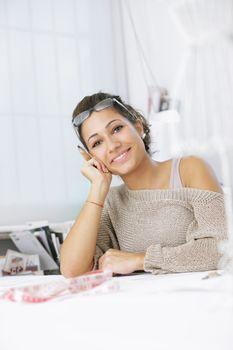 Portrait of attractive female fashion designer sitting at office desk