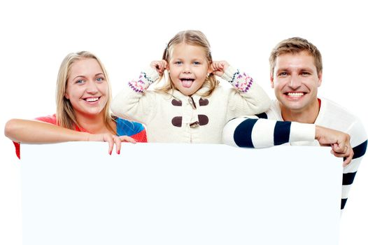 Young beautiful family behind white blank ad board. Cheerful family
