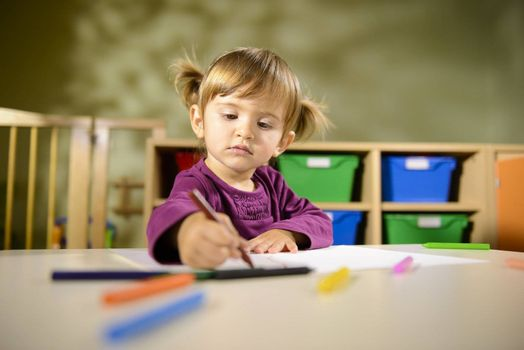 Little girl having fun at school and drawing with colors in kindergarten