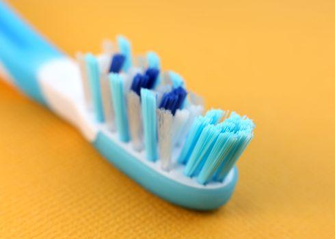 Close up shot of blue tooth brush over orange background