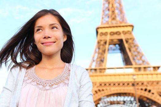 Eiffel tower Paris tourist woman smiling happy. Beautiful portrait of multiracial Asian Caucasian girl during travel in Europe.